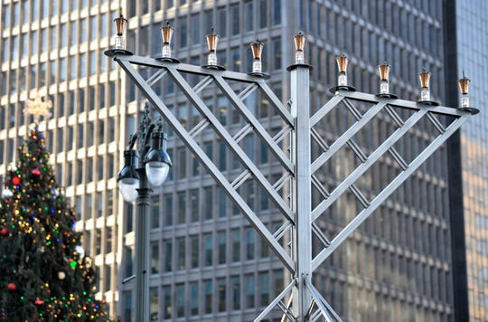 A giant glass and steel menorah is lit on the corner of Woodward and Cadillac Square in downtown Detroit. It is the centerpiece of the Menorah in the D event Sunday, the first night of Hanukkah.