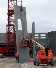 A crane positions a section of a pre-cast concrete wall at the new Wayne County Criminal Justice Complex.