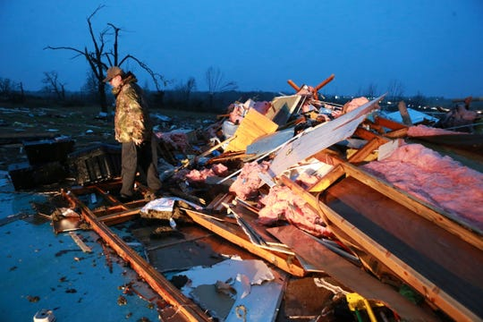 Carl Estes searches for books and other items from his church on County Road 911 that was completely destroyed by a tornado in Guntown, Miss., Monday, Dec. 16, 2019.