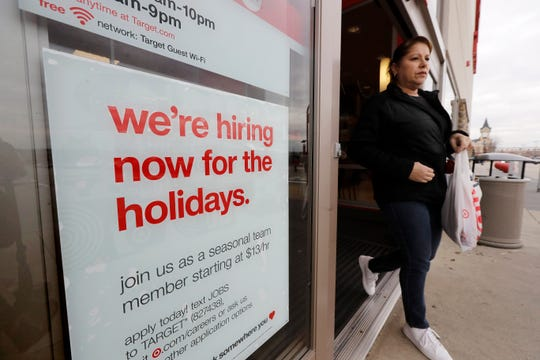 FILE - In this Nov. 27, 2019, file photo a passer-by walks past a hiring for the holidays sign near an entrance to a Target store location, in Westwood, Mass.