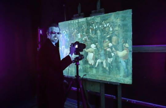 "DIA imaging specialist Aaron Steele documenting ""TheWedding Dance""under ultraviolet illumination."