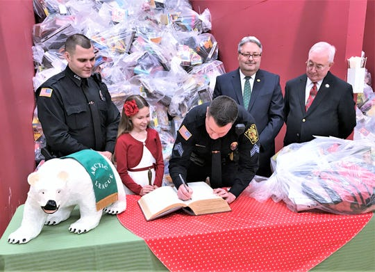 Elmira Police Department Sgt. Matt Saunders, a member of the Elmira Police Benevolent Association, makes the final entry for 2019 in the Arctic League Big Book on Tuesday. Looking on are, from left, Officer Adrian Smith, bell ringer Lylie Colunio, Arctic League Treasurer Mike Wayne and board President Michael S. Smith.