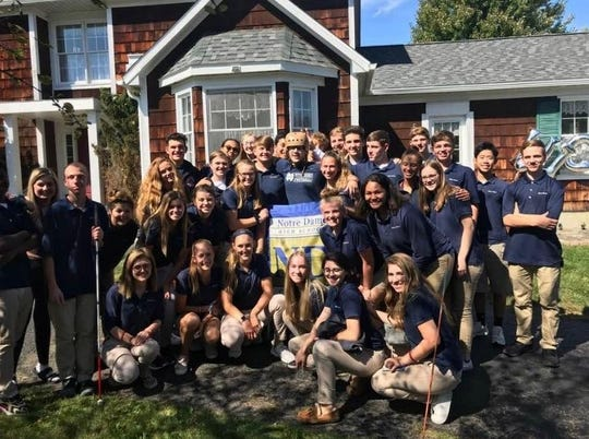 Nick Viselli, center with helmet, is surrounded by Elmira Notre Dame classmates at his Elmira home after returning from the Golisano Restorative Neurology & Rehabilitation Center on Sept. 20, 2019.