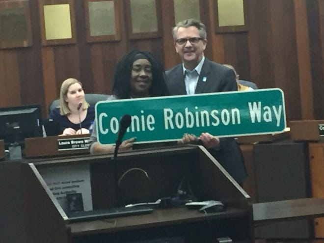 Evansville Mayor Lloyd Winnecke surprised retiring City Council member Connie Robinson on Monday with an announcement that Canal Street between Governor and Walnut streets will be named in her honor. City Clerk Laura Windhorst, left, looks on.