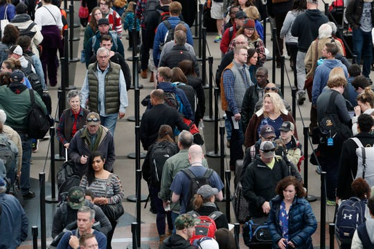 Travelers wait to pass through a security checkpoint at Denver International Airport in Denver in this 2018 file photo.