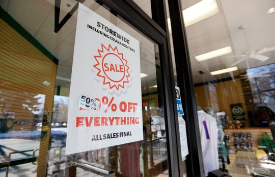 Signs advertise large discounts as Rams Book Store prepares to close in Fort Collins, Colo. on Tuesday, Dec. 17, 2019.