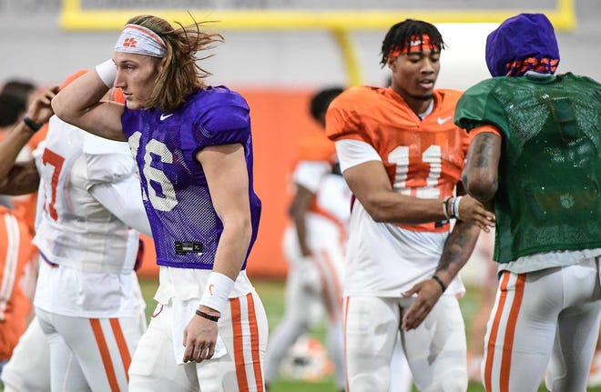 Clemson quarterback Trevor Lawrence (16) walks near safety Isaiah Simmons (11) and wide receiver Tee Higgins (5) greeting each other before practice for the College Football Playoff semi-final game at Poe Indoor Facility in Clemson, S.C. Tuesday, December 17, 2019. Clemson plays Ohio State University December 28 in Glendale, Arizona.