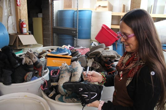 Shoes of every size and style fill plastic barrels in a back room at the Salvation Army. Store Manager Edie Boettcher prepares one pair for sale.