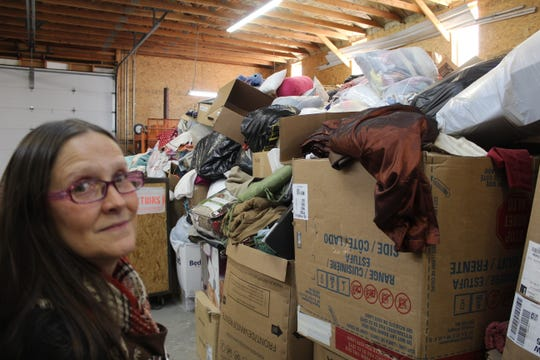 Manager Edie Boettcher considers the mound of donated items Salvation Army staff have yet to sort through