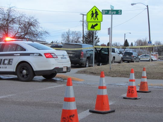 Police investigate the scene of an officer-involved shooting near Lincoln Elementary School Tuesday. The suspect, identified Wednesday at Ricky Lee Gardipee, 41, was being sought in connection with a triple homicide at the Emerald City Casino.