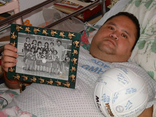 In this November 2002 file photo, Blaine Afaisen shows a photograph of the 1984 Notre Dame High School championship team and a volleyball signed by co-workers from M.U. Lujan Elementary School at his home in Inarajan.