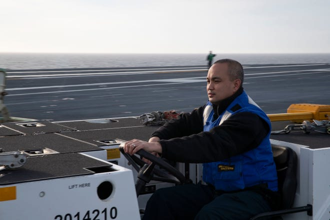 Atlantic Ocean: Aviation Boatswain's Mate (Handling) Second Class Opie Madlangbayan, from Yigo, assigned to USS Gerald R. Ford's (CVN 78) air department, drives an aircraft towing tractor on the ship's flight deck on Dec. 10. Ford is currently underway conducting an independent steaming exercise.