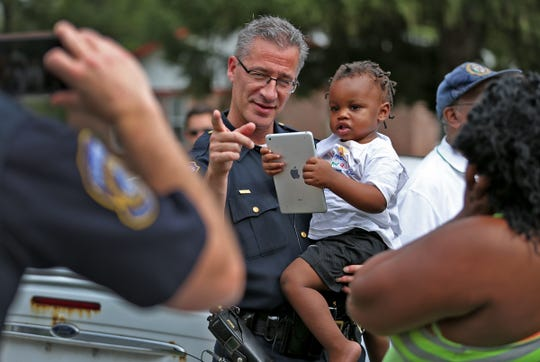 IMPD Chief of Police Bryan Roach holds Waylon Gray IV during a community walk, Wednesday, Sept. 27, 2017.