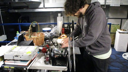"""FilmScene's head projectionist Ross Meyer prepares a reel of test footage on 35 mm film at the rewind table with his crew. They're in the projection booth at FilmScene's Chauncey location on Monday, Dec. 16. In two more days the theater will have its 35 mm debut with """"It's a Wonderful Life."""""""
