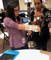 Amanda Downard, left, and Latoya Lewis, teachers at Highland Elementary School, design a cast as part of a part of teacher training for curriculum designed by Project Lead The Way.