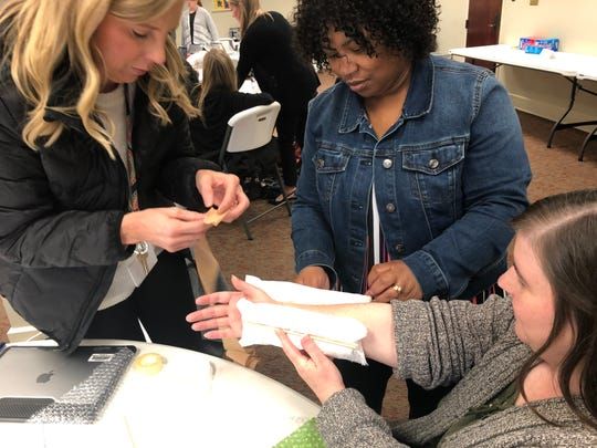 Kelly Bowles, left, Gloria Thedford and Lisa Bean, teachers at East Flora Academy, create a cast during a problem-solving exercise that is part of the curriculum designed by Project Lead The Way.