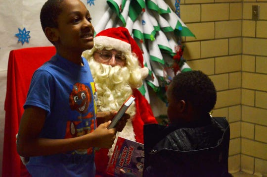 Santa gives out books to students at the Alexander Elementary School Literacy Night in Jackson, Tenn. on Dec. 10, 2019.