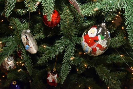 This hand painted ornament is mixed with vintage ornaments and colorful bulbs on this tree.