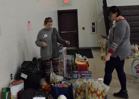 Katrina Queen, left, and her daughter Haley Bigham double check the donations gathered in the Berne Union Local Schools Community Room Dec. 17. For the past 40 years, the school and community have gathered gifts for families in need around the holidays, this year helping 29 families.
