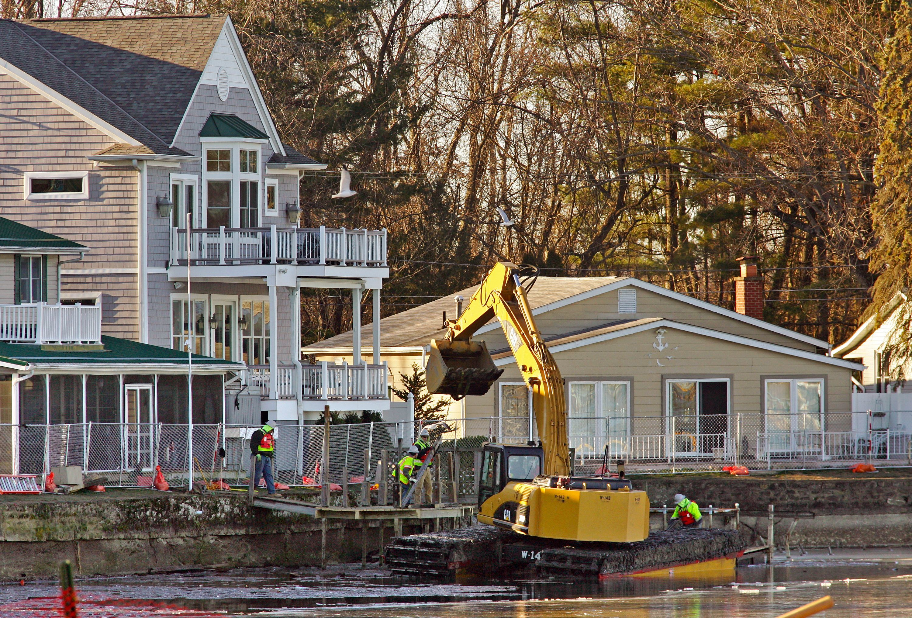 Crews use an excavator in January 2016 to lift the dock to a home on West Bank Road in Buckeye Lake.