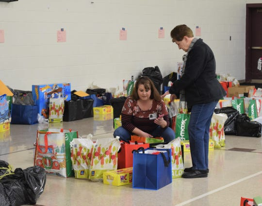 Abby Schmelzer, kneeling, and Linda Vest distribute reading books to different groups in the Berne Union Local Schools Community Room Dec. 17. For the past 40 years, the school and community have gathered gifts and goods for families in need around the holidays, this year helping 29 families.
