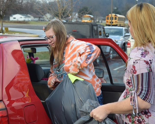 Elizabeth Ogg loads her mother's car with donated goods and gifts while Jamie Queen follows with more donations. Elizabeth's family is one of 29 benefiting with the donations from the White Christmas program.