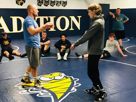 Lancaster senior Logan Agin listens to coach Dugan Bentley during practice. Agin has more than 100 career victories and is a three-time state-placer, including a state runner-up finish.