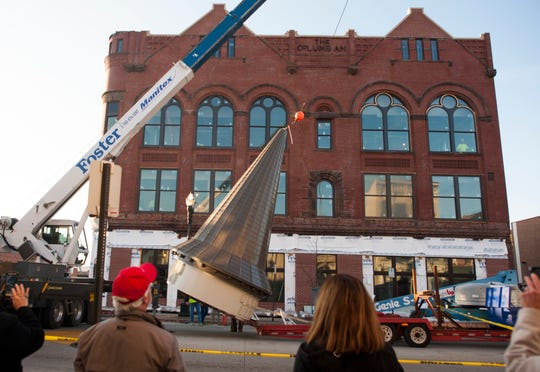 """The """"witch's hat"""" steeple is hoisted up by a crane and placed atop the corner of the Columbian Building Tuesday morning, Nov. 24, 2015, in downtown Lancaster."""