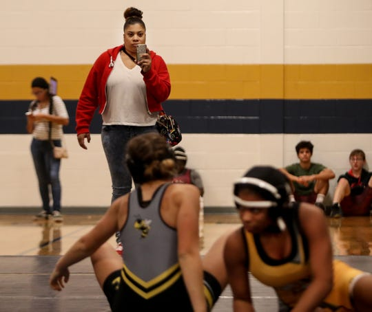Central High School's Santanna Holland, right, wrestles at Fairdale High School on Dec. 7, 2019 while her mom, Karmelle Powers, records it on her phone.