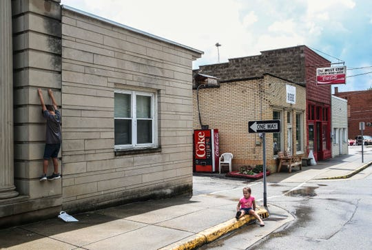 A boy hangs from the Milltown town hall — former a First National Bank — as a girl sits on the sidewalk along Main Street at the Milltown Community Festival. The small town, plotted in 1839, had about 800 people according to the 2010 census.