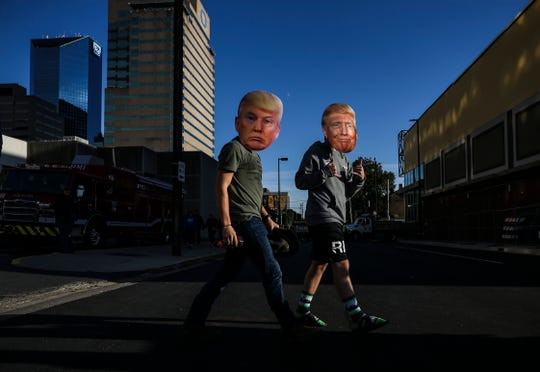 Nathan Patton, left, and Spencer Sasse of Nashville, Tennessee, wore Trump masks, Nov. 4, 2019, as they walked toward Rupp Arena to hear President Donald Trump speak and lend support to Kentucky Gov. Matt Bevin in Lexington, Kentucky.