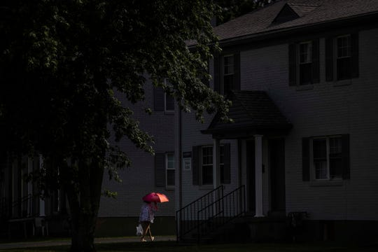 A woman walks near the Elements apartment complex that houses many multicultural families near South Third Street and behind the Iroquois Manor shopping complex, which features Vietnamese, Somalian and Chinese restaurants as well as several ethnic grocery stores. June 4, 2019.