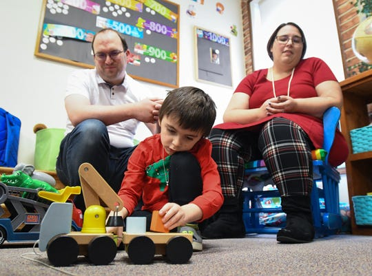 Four-year-old Eli Alchin of Bath plays in the children's section of the Bath Township Library, Tuesday, Dec. 17, 2019, while parents Marty and Angel look on.