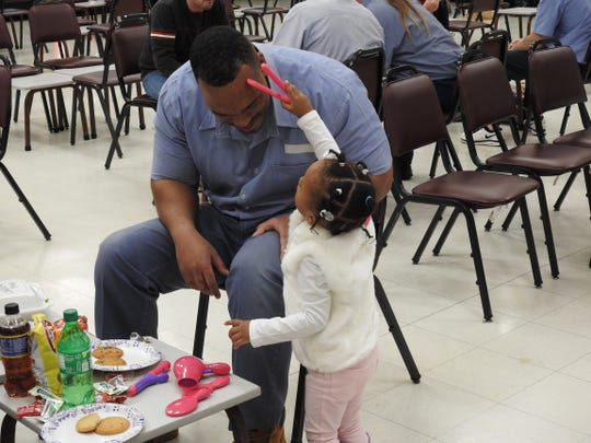 A girl grooms her father's hair during a holiday visit at Richland Correctional Institution.