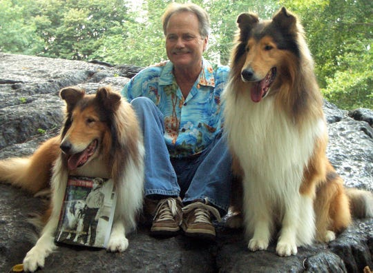 Jon Provost displays a copy of his autobiography with the help of a couple of four-legged friends.
