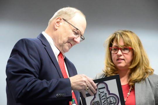 Gene Parkison, departing Lexington mayor, looks at a book with Bellville Mayor Teri Brenkus.