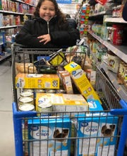 Nine-year-old Kendal Richter of West Allis is shown shopping for food for a food drive she conducted. She collected food and money from family and friends, and used the money to shop for items most-in-need at the Hunger Task Force in Milwaukee.