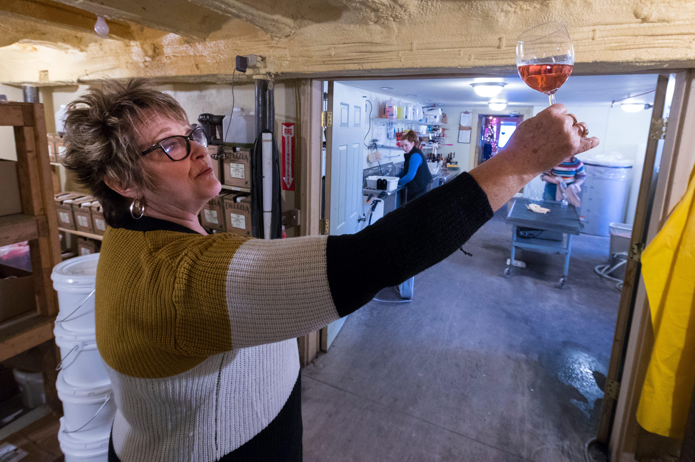 Sheri Rohland examines a glass of wine at Munson Bridge Winery.