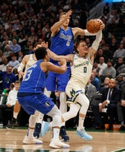 Mavericks forward Kristaps Porzingis  and Milwaukee Bucks guard Donte DiVincenzo reach for the loose ball.