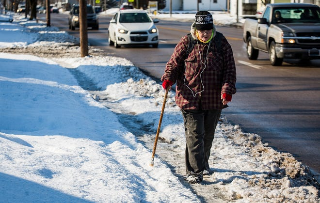 A woman with a cane traverses a snowy sidewalk on Memorial Drive Tuesday.