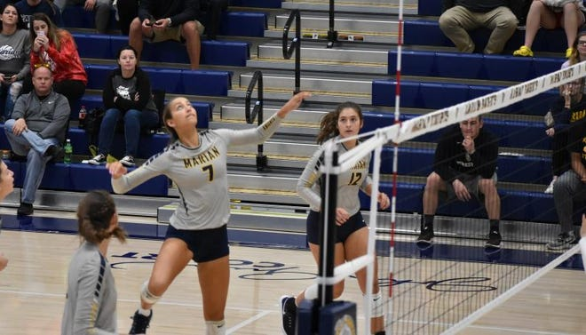 Marian's Skyler Van Note goes up for a kill.