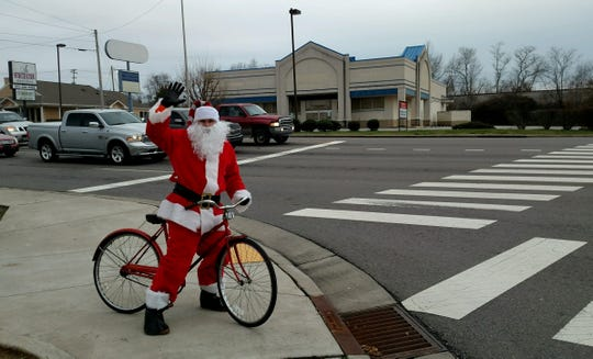 Santa (David Daniel) waves at motorists while riding a bike around Mathis and College streets, and Highway 46 South in Dickson County on Sunday.
