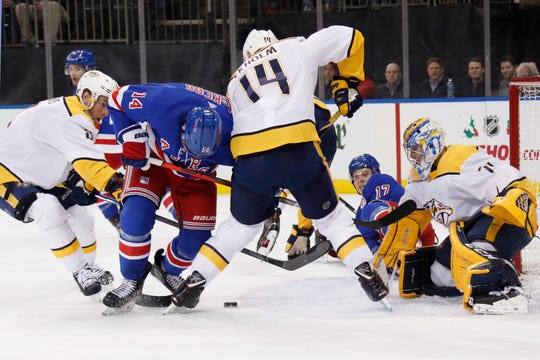New York Rangers right wing Jesper Fast (17) watches from the ice as Nashville Predators center Kyle Turris (8) and Nashville Predators defenseman Mattias Ekholm (14) try to keep the puck from Rangers center Greg McKegg (14) in front of Predators goaltender Juuse Saros (74) during the second period on Monday, Dec. 16, 2019, in New York.