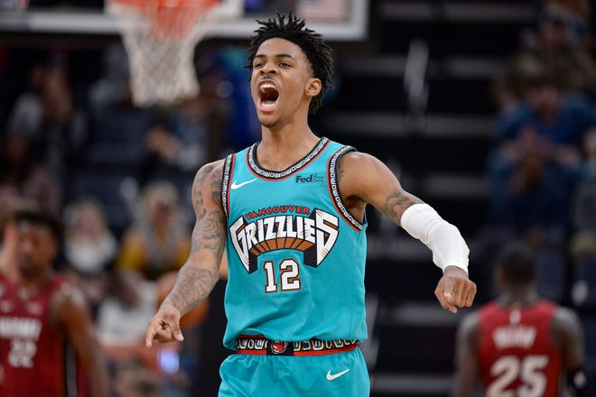 Memphis Grizzlies guard Ja Morant (12) reacts to a play in the first half against the Miami Heat.