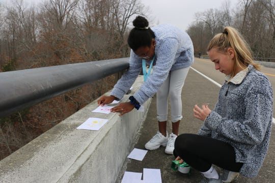 Samantha Degrasse and Keira Jenkins tape messages of hope and encouragement on the Natchez Bridge Parkway on Dec. 7, 2019.