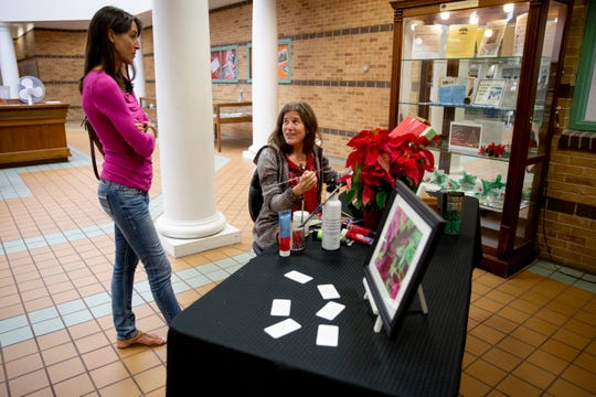 Cath Branwood, right, talks to her friend Karin Wolfe, left, while she does a live painting of a poinsettia at the Collier County Library in Naples on Monday, December 16, 2019.
