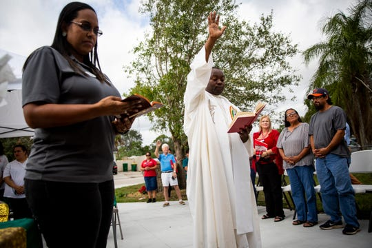 Father Wilner DuRosier from Our Lady of Guadalupe Catholic Church, center, blesses Johnny and Virginia Herrera's new house, which was built through the support of the Immokalee Unmet Needs Coalition, during a dedication ceremony in Immokalee on Tuesday, December 17, 2019. The Herreras lost their home during Hurricane Irma in 2017.