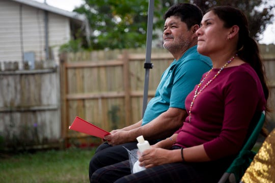 Johnny Herrera, left, and Virginia Herrera, right, listen to speakers during the dedication ceremony for their new house, which was built through the support of the Immokalee Unmet Needs Coalition, in Immokalee on Tuesday, December 17, 2019.