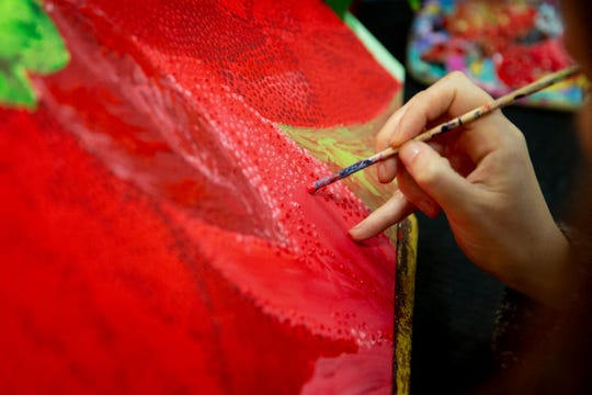 Cath Branwood does a live painting of a poinsettia at the Collier County Library in Naples on Monday, December 16, 2019.