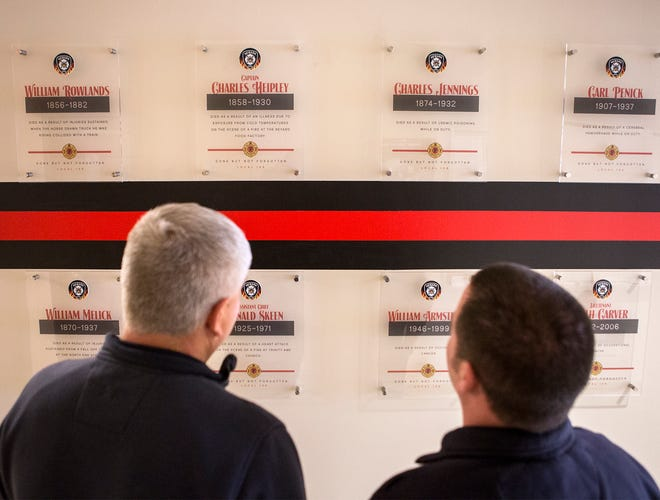 A memorial wall dedicated to honoring Newark firefighters who lost their lives in the line of duty now hangs at Fire Station 1 in Newark. Newark firefighters Doug Vermaaten and Kevin Garwick, who were instrumental in organizing the design and hanging of the memorial wall stand in front of it looking at the names and talking about the history of each of the fallen firefighters.